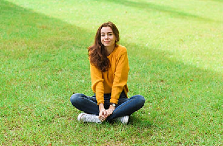 Woman with brown hair and orange jumper sitting on grass