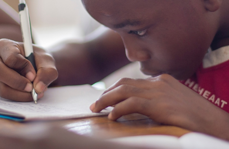 Young child writing in notebook