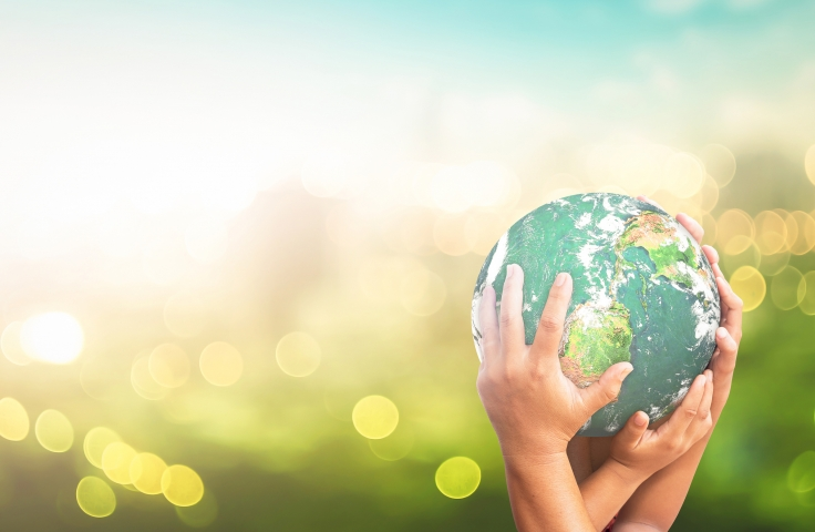 Human hands holding earth global over blurred green city background