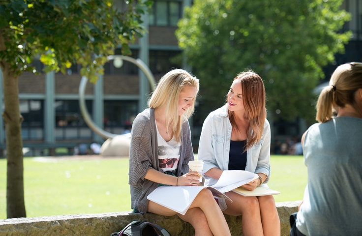 Two female students sitting by UNSW library lawn