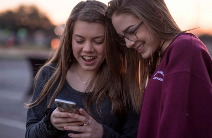 Two teenage girls looking at a phone.