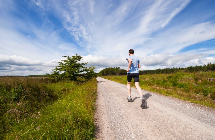 A man runs outdoors on a gravel road.