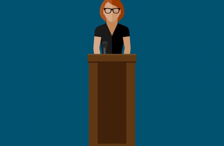 Cartoon of woman standing at lectern