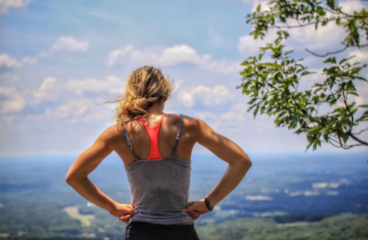 Woman wearing exercise gear, looking at view after hiking.